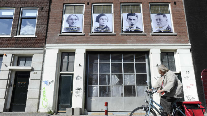 """Images of four Amsterdam Jews who died in the Holocaust are seen on a building on Kromme Waal street where they lived during the war in Amsterdam, Netherlands, Wednesday, May 4, 2011. A project called """"Jewish Houses,"""" part of Wednesday's commemorations of World War II victims, encouraged Amsterdam residents to put up posters marking the 21,662 houses where Jews are known to have lived before the community was systematically sent to die in Nazi concentration camps. (AP Photos/ Evert Elzinga)"""