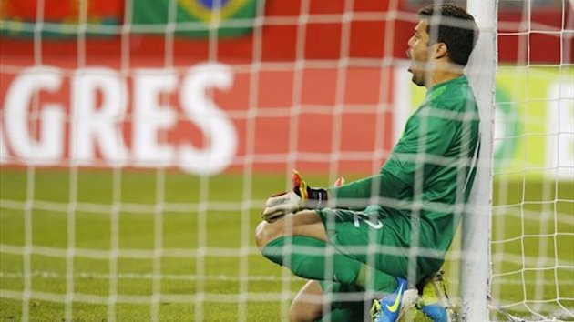 Brazil's goalkeeper Julio Cesar shouts to his team mates as they form a wall for a free kick by Portugal d