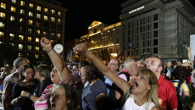 "Supporters of the No vote react after the first results of the referendum at Klafthmonos square in Athens, Sunday, July 5, 2015. Greece faced an uncharted future as officials counted the results of a referendum Sunday on whether to accept creditors' demands for more austerity in exchange for rescue loans, with three opinion polls showing a tight race with a narrow victory likely for the ""no"" side. (AP Photo/Petr David Josek)"
