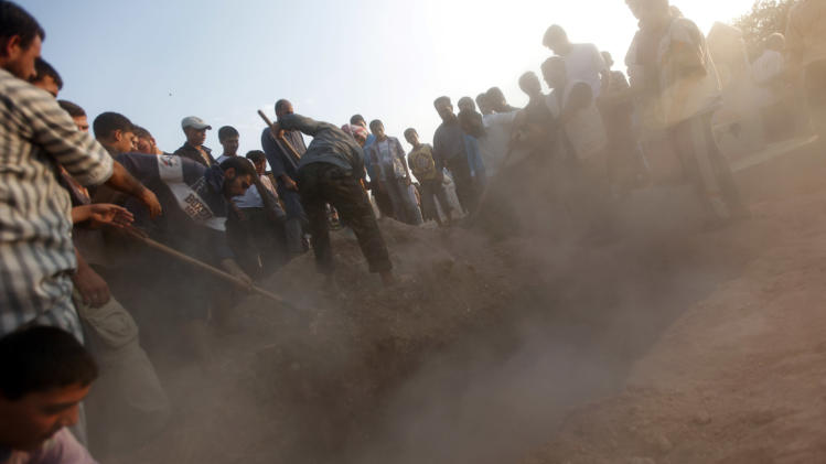 Syrians throw the earth over the grave of 29 year-old Free Syrian Army fighter, Husain Al-Ali, who was killed during clashes in Aleppo, after they buried in the cemetery in the town of Marea on the outskirts of  Aleppo city, Syria, Thursday, Aug. 9, 2012. (AP Photo/ Khalil Hamra)
