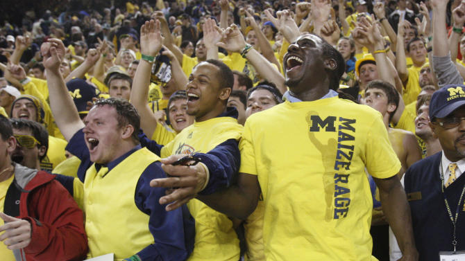 Michigan quarterback Denard Robinson, right, sitting in the Maize Rage student section, celebrates with fans after Michigan's 60-59 win over Michigan State in an NCAA college basketball game in Ann Arbor, Mich., Tuesday, Jan. 17, 2012. (AP Photo/Carlos Osorio)