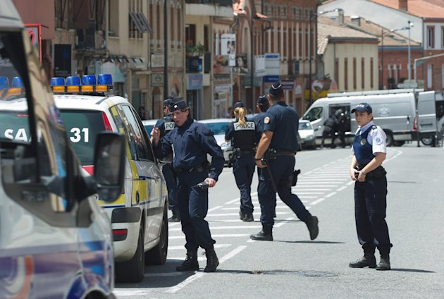 Police officers control the street next to a bank where a man took hostages  in the southern French city of Toulouse, Wednesday, June 20, 2012. A gunman who authorities say had past psychiatric proble