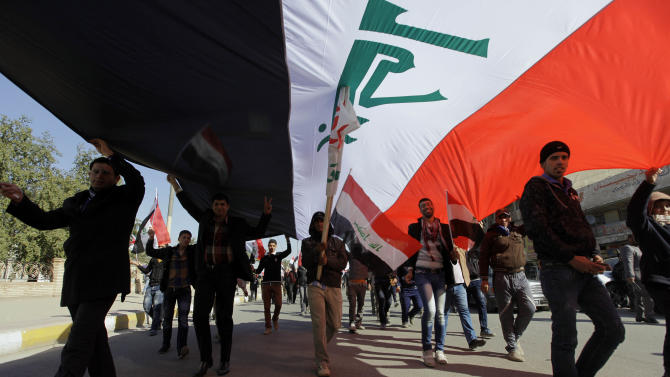 Protesters chant pro-Iraqi Prime Minister Nouri al-Maliki slogans as they carry a huge Iraqi flag during a demonstration to show support for Al-Maliki's government, in Baghdad, Iraq, Jan. 12, 2013. Shiite demonstrators are taking to the streets in Iraq's capital to show support for the prime minister who has been facing angry protests in Sunni provinces for the past three weeks as the Sunni minority protest what they call discrimination by the Shiite-led government. (AP Photo/Khalid Mohammed)