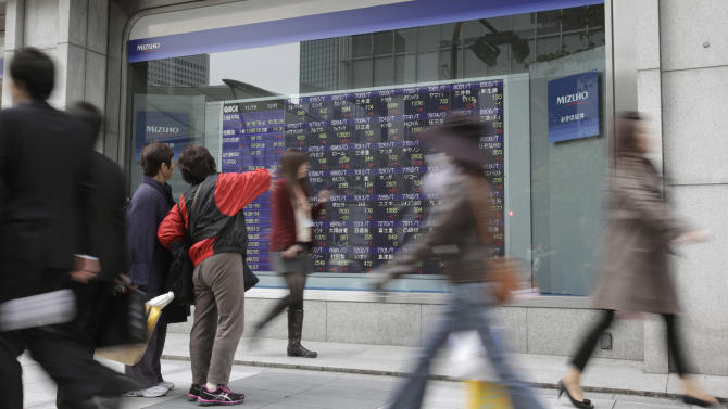 Women check an electronic stock indicator in Tokyo, Monday, Nov. 19, 2012 as the yen's recent weakness helped boost Japan's Nikkei 225 and its heavy orientation toward exporting companies. The index in Tokyo jumped 1.6 percent to 9,171.26, a two-month high. (AP Photo/Shizuo Kambayashi)
