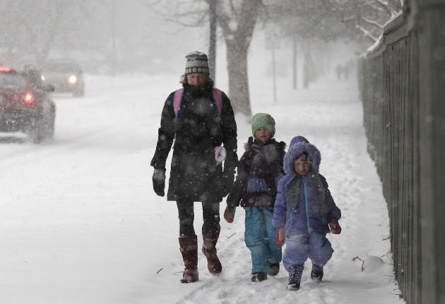 Linda Jones walks her daughters Sophie and Zoe to school as a blizzard dropped snow over Boulder, Colo., Wednesday Dec. 19, 2012. A storm that has dumped more than a foot of snow in the Rocky Mountain