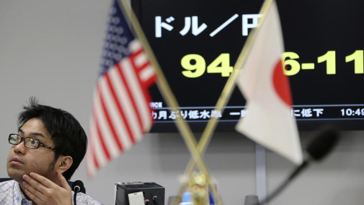 A foreign exchange broker works in front of a screen displaying the current dollar to yen rate as an American, left, and Japanese, right, flag are displayed at the office in Tokyo, Monday, Feb. 18, 2013. Last week, the yen fell to a near three-year low against the dollar and the euro.  (AP Photo/Koji Sasahara)