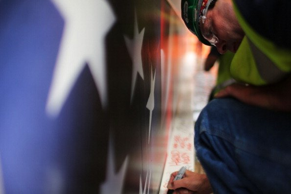 Construction worker Ken Apple signs the last steel beam, along with other members of the crews that helped build the tower, before it is hoisted 977 feet to the top of Four World Trade Center on June
