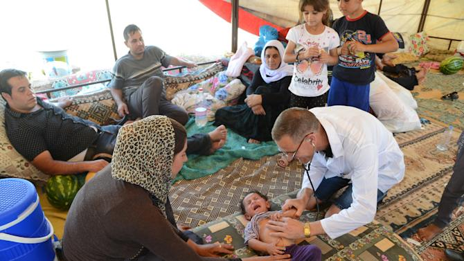 A doctor checks a Iraqi baby from the Yazidi community in a refugee camp near the Turkey-Iraq border at Silopi in Sirnak on August 14, 2014