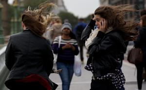 Wind catches the hair of two women crossing Westminster …