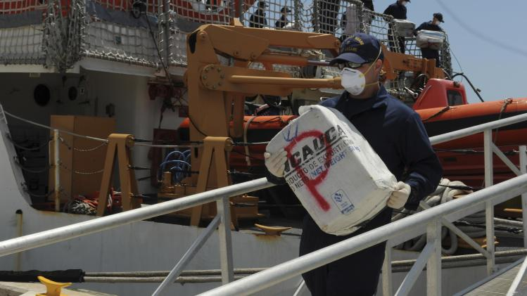 A crew member aboard the Coast Guard Cutter Legare offloads a bale of cocaine at Coast Guard Base Miami Beach