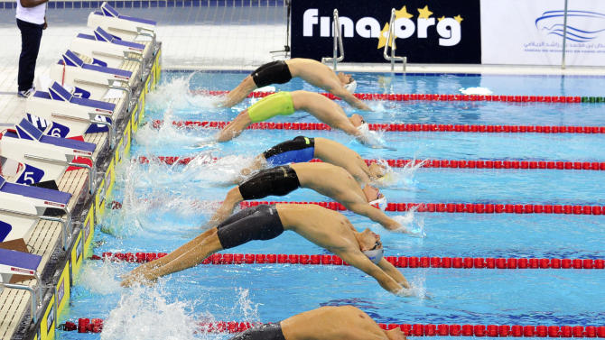 Swimmers start in the men's 100-meter backstroke at the FINA/ARENA Swimming World Cup, in Dubai, United Arab Emirates, Tuesday, Oct 2, 2012. (AP Photo/Stephen Hindley)