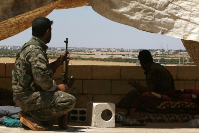 Fighters of the Syria Democratic Forces (SDF) sit in a look out position in the western rural area of Manbij, in Aleppo Governorate, Syria, June 13, 2...