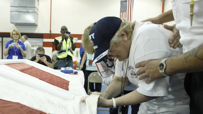 Sylvia Wasylyk cries as she touches the National 9/11 Flag during a sewing the West Virginia restorative patch ceremony at the Martinsburg VA Medical Center in Martinsburg, W.Va. on Tuesday, June 21, 2011. (AP Photo/Luis M. Alvarez)