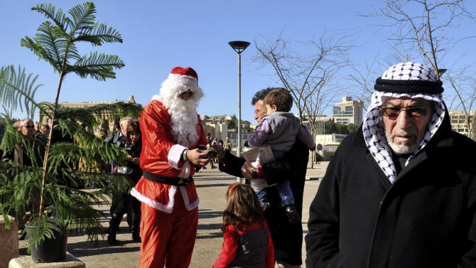 A man dressed as Santa Claus distributes Christmas trees to Christians outside Jaffa Gate in the Old City of Jerusalem, Sunday, Dec. 23, 2012. (AP Photo/Mahmoud Ilean)