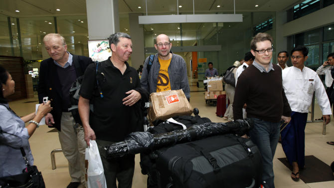 Farmer and businessman David Cundall, second from left, of Britain, arrives with his team of British excavators at Yangon International airport on Sunday, Jan. 6, 2013, in Yangon, Myanmar. The team arrived in Myanmar to begin the first of several digs they hope will unearth dozens of rare British fighter planes said to have been buried in the Southeast Asian country at the end of World War II. (AP Photo/Khin Maung Win)
