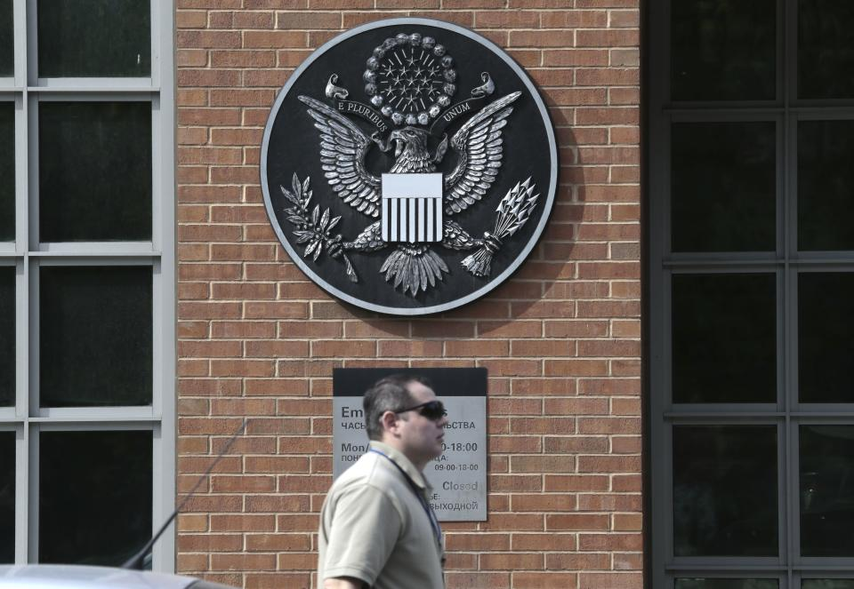 A man passes an entrance of the U.S. Embassy  in downtown Moscow, Russia, on Tuesday, May 14, 2013. Russia's security services said Tuesday that they detained a U.S. diplomat they claim is a CIA agent after they caught him red-handed trying to recruit a Russian agent. (AP Photo/Ivan Sekretarev)