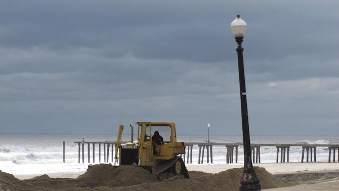 A bulldozer pushes piles of sand around on the Ocean Grove N.J. beach in front of its storm-buckled boardwalk and damaged fishing pier on Nov. 15, 2012.  Superstorm Sandy took a bite out of the Jersey shore, washing away millions of tons of sand and slimming down beaches along the state's 127-mile coastline. (AP Photo/Wayne Parry)