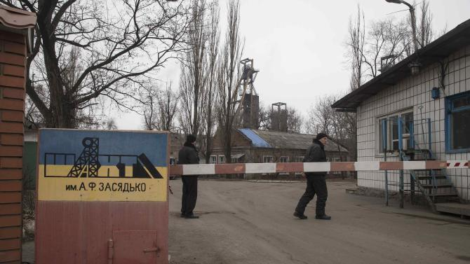 Men stand at the gate to Zasyadko coal mine in Donetsk