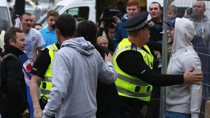 A pro-independence protestor is restrained by police as he tussles with pro-union protestors during a demonstration at George Square in Glasgow