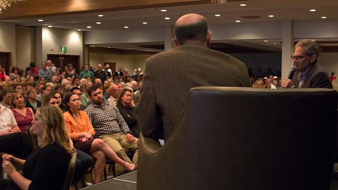 """In this photo provided by Jacob Green, author author John Krakauer, right,speaks about his book """"Missoula: Rape and the Justice System in a College Town"""" to a crowd of more than 550 people at a forum open to the public, Wednesday evening, May 6, 2015, in Missoula, Mont. The Missoula audience gave the best-selling author of the book about the city's mishandling of rape cases a standing ovation Wednesday and then booed a heckler who had elbowed his way to the stage and called Krakauer a liar. (Jacob Green via AP)"""