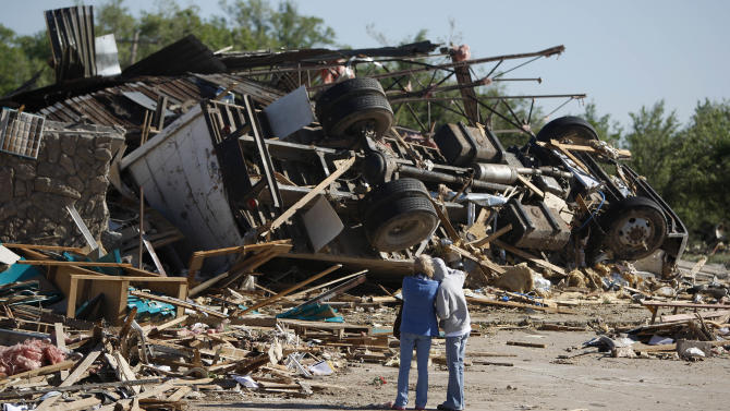 People stand by the remains of a business after a tornado struck Woodward, Okla., Sunday, April 15, 2012. More than 100 tornadoes had been reported across the region by daybreak, according to the National Weather Service. (AP Photo/The Oklahoman, Bryan Terry)