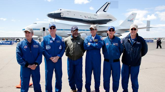 FILE - In this April 27, 2012, file photo, the crew of the space shuttle Enterprise, from left, Ace Beall, Henry T. Taylor, Darrell Hood, Bill Rieke, Larry LaRose and Jeff Moultrie pose for a photo after their last flight with the shuttle at JFK International Airport in New York. Enterprise has been separated from the NASA 747 Shuttle Carrier at John F. Kennedy International Airport, just weeks after flying over New York City. Next month it will be taken by barge to the aircraft carrier USS Intrepid, the floating air-and-space museum that will be the shuttle's permanent home. The shuttle is scheduled to open to the public in mid-July. (AP Photo/John Minchillo, File)