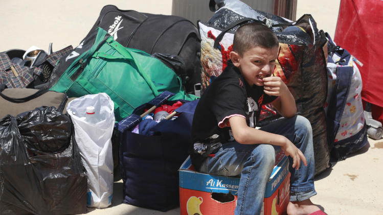 A Syrian refugee boy sits beside bags as he arrived at the border crossing by the Iraqi town of Qaim, 200 miles (320 kilometers) west of Baghdad, Iraq, Tuesday, Aug. 7, 2012. (AP Photo/Hadi Mizban)