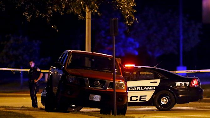 A police officer stands near a vehicle after a shooting outside the Muhammad Art Exhibit and Contest in Garland, Texas