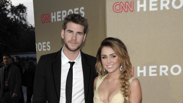 Actor Liam Hemsworth, left, and actress and singer Miley Cyrus arrive at the Fifth Annual CNN Heroes: All-Star Tribute in Los Angeles on Sunday, Dec. 11, 2011. (AP Photo/Dan Steinberg)