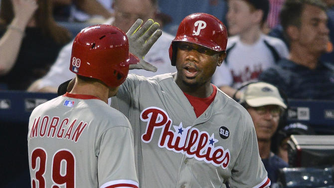 Philadelphia Phillies' Ryan Howard high-fives Adam Morgan (39) after Morgan scored on a Cesar Hernandez hit during the fifth inning of a baseball game against the Atlanta Braves on Friday, July 3, 2015, in Atlanta. (AP Photo/Jon Barash)