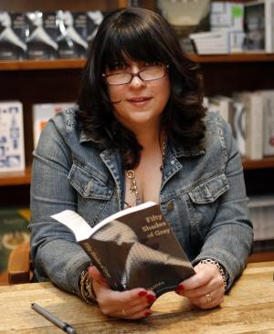 "Author E L James holds a copy of her new erotic fiction book ""Fifty Shades of Grey"" at a book signing in Coral Gables, Fla., Sunday, April 29, 2012. (AP Photo/Jeffrey M. Boan)"