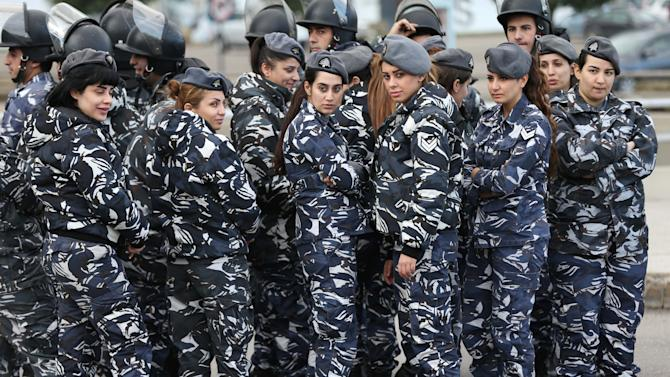 Lebanese policewomen stand behind riots police during a demonstration for the families of Lebanese soldiers who kidnapped by Islamic militants, a day after the Nusra Front threatened to kill one of the soldiers, and demanding that the government negotiate seriously with the militants, in downtown Beirut, Lebanon, Friday, Nov 28, 2014. Police have used water cannons to break up a protest by relatives of Lebanese soldiers held hostage by Islamic militants, during which they closed off a main highway in the capital. Several of the protesters and journalists were also beaten up a security forces sought to reopen the road. (AP Photo/Hussein Malla)