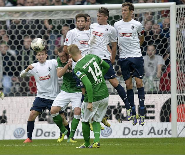 Freiburg's defense jumps for a free kick of Bremen's Aaron Hunt, front, during the German first division Bundesliga soccer match between Werder Bremen and SC Freiburg in Bremen, Germany, Saturday, Oct