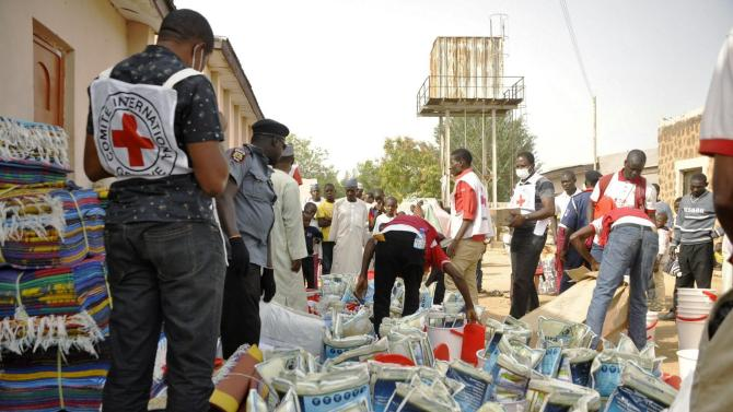 Red Cross members distribute relief materials to displaced victims of the Boko Haram violence at a relief camp in Dawaki