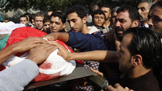 Palestinians carry the body of Osama Shehada, 17, during his funeral in the Nuseirat Refugee Camp, central Gaza Strip, Tuesday, Nov. 20, 2012. Shehada was killed in an Israeli air strike on Monday while walking with his uncle in the camp, neighbors said. (AP Photo/Adel Hana)