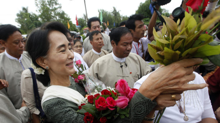 FILE - In this July 27, 2013, file photo, Myanmar opposition leader Aung San Suu Kyi receives flowers from her supporters upon arrival to attend the opening ceremony of a central library at Kaw Hmu township in Yangon, Myanmar. The Obama administration wants to restart U.S. defense training for Myanmar that was cut 25 years ago after a bloody crackdown on protesters. With the backing of opposition leader Aung San Suu Kyi, U.S. defense legal experts last week made their second trip to Myanmar in two months, scoping out what help they can provide on teaching about human rights and rule of law. (AP Photo/Khin Maung Win, File)