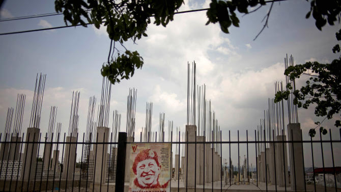 "In this April 8, 2013 photo, an image of Venezuela's late President Hugo Chavez is posted on an iron fence next to a government construction project of would be homes in Valencia, Venezuela. Outside Venezuela's capital, power outages, food shortages and unfinished projects abound; important factors heading into Sunday's election to replace socialist Chavez, who died last month after a long battle with cancer. An estimated 2 million of Venezuela's country's nearly 30 million people lack permanent homes, and one of Chavez's anti-poverty ""missions"" builds them. But it's been slow going. The government says it has built 370,500 homes and apartments over the past two years, and more than 3 million people applied for them. (AP Photo/Ramon Espinosa)"
