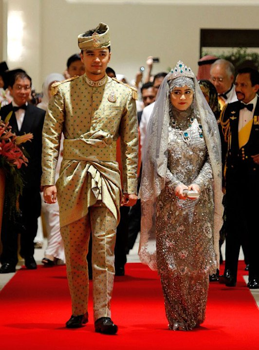 Brunei's newly wed royal couple Princess Hajah Hafizah Sururul Bolkiah (R) and her groom Pengiran Haji Muhammad Ruzaini arrive for their wedding banquet in Bandar Seri Begawan on September 23, 201