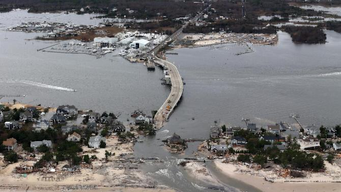 FILE - This Wednesday, Oct. 31, 2012 file aerial photo made from a helicopter shows storm damage from Superstorm Sandy over the Atlantic Coast in Mantoloking, N.J. Humans have an affinity for water. But in these recent jumbled days, the collapsed houses, flooded subway tunnels and washed-out roads left in Sandy's wake remind us once again: Our deep-seated human desire to be near the water _ to be attracted and comforted by it, to build alongside it and crave its attractions _ has an undeniable dark side. (AP Photo/Doug Mills, Pool, File)
