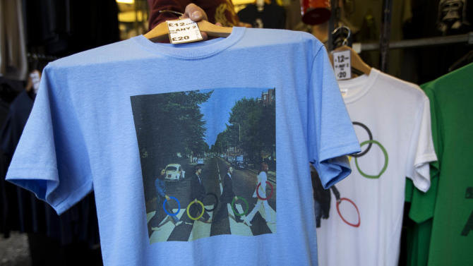 "In this photo taken Monday, July 16, 2012, a t-shirt with featuring the cover photograph from the album ""Abbey Road"" printed on it, shows The Beatles holding Olympic rings as they walk across the zebra crossing as it sold at a London market. The guardians of the games are vigilant about protecting the integrity - and the commercial clout - of the Olympic brand. But even they can't stop the irreverent spirit of artists and craftspeople, who have responded to the games with a cheeky mix of celebration, skepticism and satire. (AP Photo/Matt Dunham)"