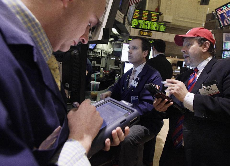 Trader Edward Schreier, right, works with specialist John Alatzas, center, on the floor of the New York Stock Exchange Friday, Feb. 3, 2012. U.S. stocks are opening sharply higher after the unemployment rate dropped to the lowest in two years. (AP Photo/Richard Drew)