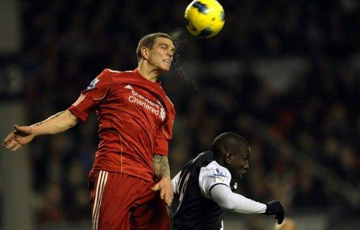 Daniel Agger (left) beats Newcastle United's forward Demba Ba to the ball