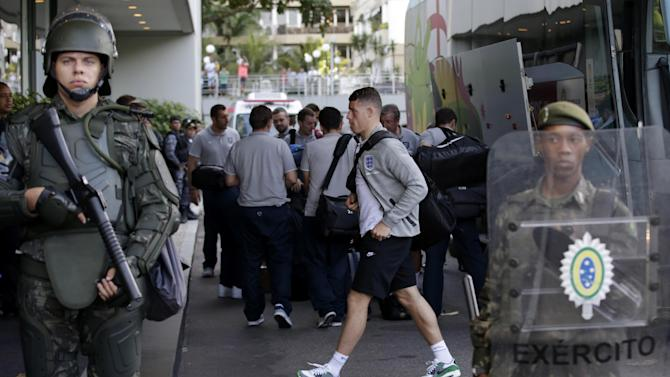 England's national soccer team player Ross Barkley walks past members of the Brazilian army standing on guard as the players got off the team coach upon their arrival at the squad's hotel for the 2014 soccer World Cup in Rio do Janeiro, Brazil, Sunday, June 8, 2014