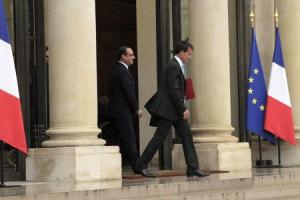 French President Hollande watches as Prime Minister Valls leaves after their meeting at the Elysee Palace in Paris