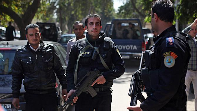 Egyptian police officers take positions during the arrest of Ahmed Qaddaf al-Dam, cousin of Libya's former dictator Moammar Gadhafi, not pictured, in Cairo, Egypt, Tuesday, March 19. 2013. Egyptian security forces arrested a cousin of Libya's former dictator Moammar Gadhafi on Tuesday following an hours-long siege of his home in central Cairo, a security official and witnesses said. (AP Photo/Khalil Hamra)
