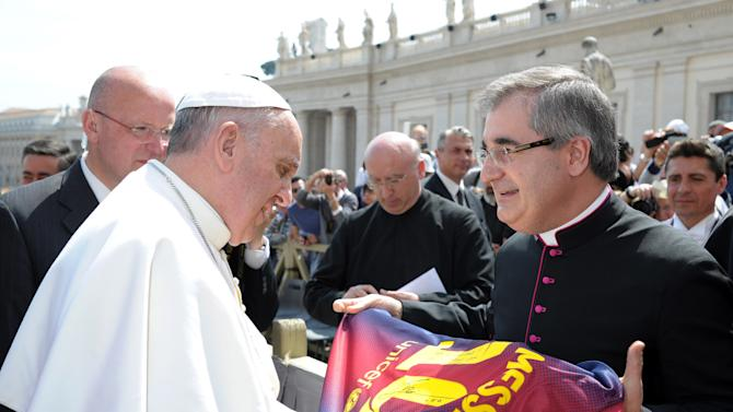 In this photo provided by the Vatican paper L'Osservatore Romano and made available Thursday, April 18, 2013, Mons. Miguel Delgado Galindo presents a jersey of Argentine soccer star Lionel Messi to Pope Francis, at the Vatican Wednesday, April 17, 2013. (AP Photo/L'Osservatore Romano, ho)
