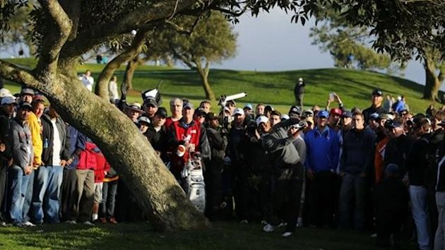 Tiger Woods bends his shot around a tree on the 4th fairway during weather delayed fourth round play at the Farmers Insurance Open in San Diego, California, January 27, 2013