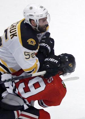 """In this photo taken June 22, 2013, Chicago Blackhawks center Jonathan Toews, bottom, takes a hit above the shoulders from Boston Bruins defenseman Johnny Boychuk during second period in Game 5 of the NHL hockey Stanley Cup Finals in Chicago. Patrice Bergeron may or may not be available for the Bruins in Game 6 of the Stanley Cup final, but Claude Julien is keeping that a secret. Toews' status for the Blackhawks might be a little clearer. Julien called Bergeron day-to-day with a """"body"""" injury and added that his status was """"really good news."""" (AP Photo/Charles Rex Arbogast)"""