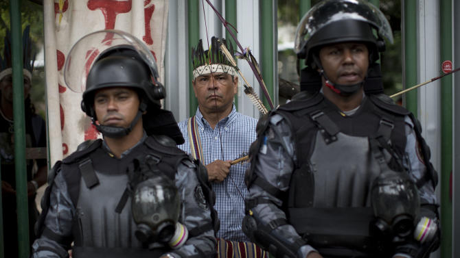 An Indian man wearing a headdress and holding a bow and arrow stands behind two policemen in riot gear on the site of an old Indian museum, in Rio de Janeiro, Brazil, Saturday, Jan. 12, 2013. Police on Saturday surrounded the site, now an indigenous settlement of men and women living in 10 homes, and prepared to enforce their eviction. The settlement is next to the Maracana stadium, which is being refurbished to host the opening and closing ceremonies of the 2016 Olympics and the final match of the 2014 World Cup. The streets around the stadium will also undergo a vast transformation as part of the area's transformation into a shopping and sports entertainment hub. (AP Photo/Felipe Dana)
