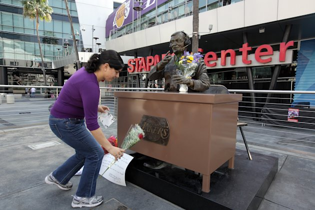 Lakers fan Jeannette Hernandez, lays a flower at the statue of the late Laker announcer Chick Hearn for Lakers' owner Jerry Buss at the Staples Center in downtown Los Angeles on Monday Feb. 18,2013. B